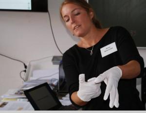 Alexa Matuschek demonstriert beim Trainingsworkshop den GIZ-Teilnehmern das fachgemäße Ausziehen von Schutzhandschuhen. Foto: Elke Blüml/Missionsärztliches Institut