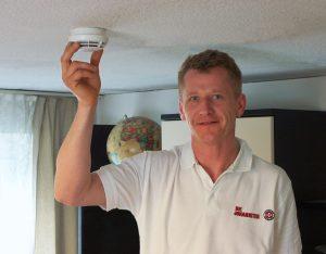 Kleine Lebensretter an der Decke: Hausnotruf-Experte Mario Fischer installiert einen seniorengerechten Rauchmelder im Wohnzimmer. Foto: Christoph Fleschutz / Johanniter
